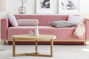 Pink sofa with patterned pillows and wooden coffee table with ar